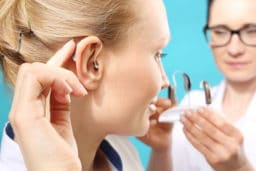 Young woman being fitted with a hearing aid