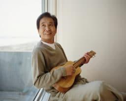 Senior man sitting by window playing ukelele, looking up