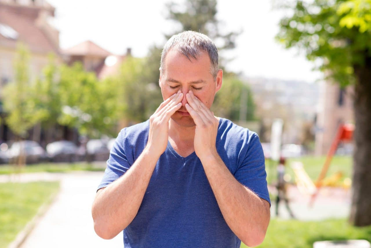 Man with congestion holds his nose