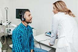Middle age man at medical examination or checkup in otolaryngologist's office