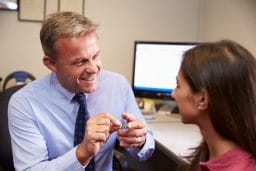 Woman with hearing aids speaks with her audiologist.